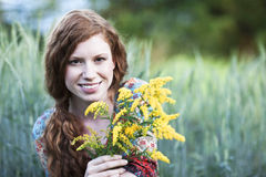 Young smiling woman with yellow flowers Royalty Free Stock Photos