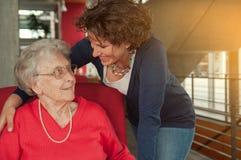 Young smiling woman embracing senior woman stock photo