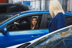 Young smiling woman getting keys of a new car. Concept for car rental stock photography