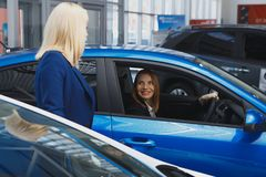 Young smiling woman getting keys of a new car. Concept for car rental stock photos