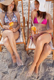 Young smiling women holding exotic cocktails. While looking at each other Royalty Free Stock Photography