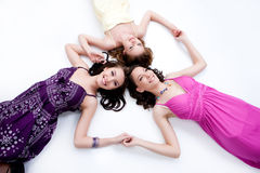 Young Smiling Women. Three young smiling women lying on a studio background stock images