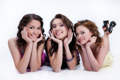 Young Smiling Women. Three young smiling women lying on a studio background stock photography