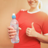 Young smilingl woman holding plastic bottle. Thumbs up. Focused Royalty Free Stock Photo