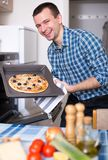 Man preparing delicious pizza in oven. Young smilingman preparing delicious pizza in oven at home Stock Photos