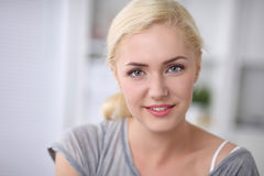 Young smilling beautiful woman sitting on couch at Stock Photography