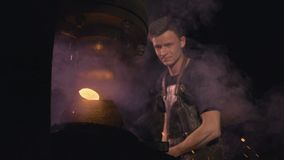 A young smith close up. A smith is working in a smithy close up