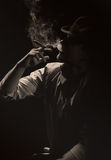 Young smoking man in the dark Stock Photos