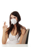 Young smoking woman with face mask Stock Images
