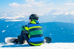 Young with a snowboard man sitting on the top of the mountain in Alps watching into the horizon. Saalbach, Austria. March 20, 2018. young with a snowboard man stock photography