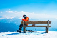 Young with a snowboard man sitting on the top of the mountain. Saalbach, Austria. March 20, 2018. young with a snowboard man sitting on the top of the mountain stock images