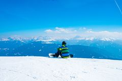 Young with a snowboard man sitting on the top of the mountain. Saalbach, Austria. March 20, 2018. young with a snowboard man sitting on the top of the mountain royalty free stock photography