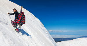 Young snowboarder climbing up the slope Stock Image