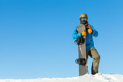 Young snowboarder in helmet at the very top of a snowy mountain with beautiful blue sky on background Stock Photography