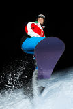 Young snowboarder jumping at night Stock Photo
