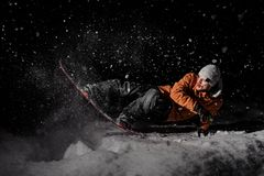 Young snowboarder in orange jacket riding on a snowy hill at night. Young snowboarder in orange jacket riding on a snowy powder hill at dark night on black stock image