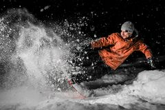 Young snowboarder in orange sportswear jumping on the board at n. Young snowboarder in orange sportswear and jumping on the board in the powder snow at night stock photo