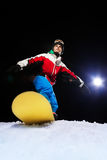 Young snowboarder ready to slide at night Stock Images