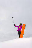 Young snowboarder shooting a selfie by her cell phone Royalty Free Stock Image