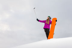 Young snowboarder shooting a selfie by her cell phone Royalty Free Stock Photos