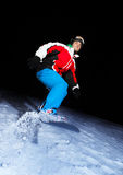 Young snowboarder sliding at night Stock Photos