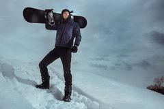 Young snowboarder standing on hill and holding board for snowboarding. Atmospheric image winter sports concept. Young snowboarder standing on hill and holding Royalty Free Stock Photos