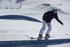 Young snowboarder woman sliding on a box. Royalty Free Stock Photo