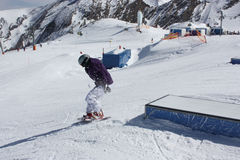 Young snowboarder woman sliding on a box. Royalty Free Stock Photography