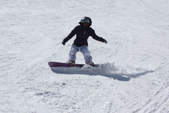 Young snowboarder woman sliding downhill. Royalty Free Stock Image