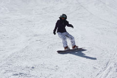 Young snowboarder woman sliding downhill. Stock Image