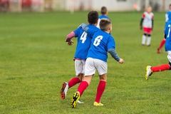 Young soccer boys huging during football match. On the field stock photo