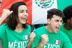 Young soccer fans from Mexico with mexican flag. Outdoors at stadium stock photography