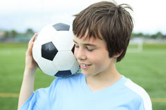 Young soccer player with ball on the field Royalty Free Stock Photography