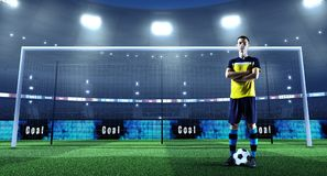 Young soccer player with ball in front of the goal on a professi stock photo