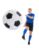 Young soccer player in blue kicking ball isolated on white backg Stock Photography