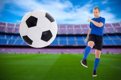 Young soccer player in blue uniform kicking ball on the stadium Stock Photography