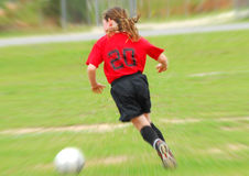 Young soccer player chasing ball Stock Images
