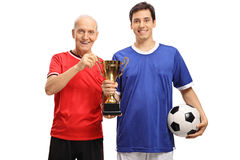 Young soccer player and an elderly player holding golden trophy Stock Image