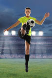 Young Soccer Player. Young female soccer player playing inside large stadium at dusk Royalty Free Stock Photography