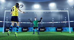 Young soccer player is kicking ball while goalkeeper defends on royalty free stock photos
