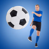 Young soccer player kicking ball over blue Royalty Free Stock Image