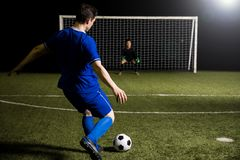 Footballer shooting a penalty kick. Young soccer player taking a penalty kick against a blurred goalkeeper in the goal royalty free stock image