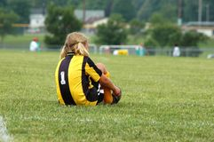 Young Soccer Player Ties Shoes. Young girl soccer player ties shoes on break Royalty Free Stock Photos
