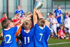 Young Soccer Players Holding Trophy. Boys Celebrating Soccer Football Championship. Winning team of sport tournament for kids children royalty free stock image