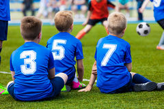 Young soccer team. Reserve players sitting together and watching Royalty Free Stock Photos