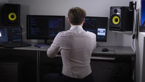 Young software developer analyzes and introduces a large amount of electronic data while working on a new software. Project. A couple of monitors and a laptop stock footage