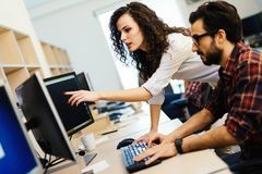 Software engineers working on project and programming in company. Young software engineers working on project and programming in company royalty free stock image