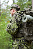 Young soldier with backpack in forest Stock Photo