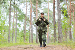 Young soldier with backpack in forest. War, hiking, army and people concept - young soldier or ranger with backpack walking in forest Royalty Free Stock Images
