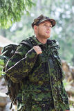 Young soldier with backpack in forest Royalty Free Stock Image